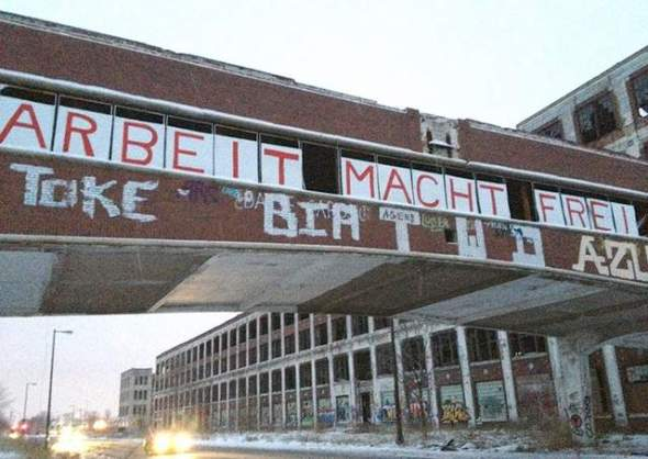 """Someone hung letters to make a sign that said Arbeit macht frei -- """"Work makes you free, """" or """"Work sets you free, """" on the Packard Plant. Photo taken Monday, Feb. 4, 2013. A sign with the same saying is on the gate at the Auschwitz concentration camp. / Niraj Warikoo/DFP"""